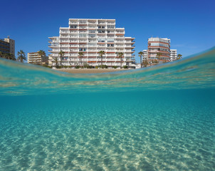 Beachfront buildings and sandy seabed underwater, split view above and below water surface, Mediterranean sea, Spain, Costa Brava, Roses, Catalonia, Girona