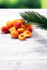 Bunch of fresh apricots on wooden table.