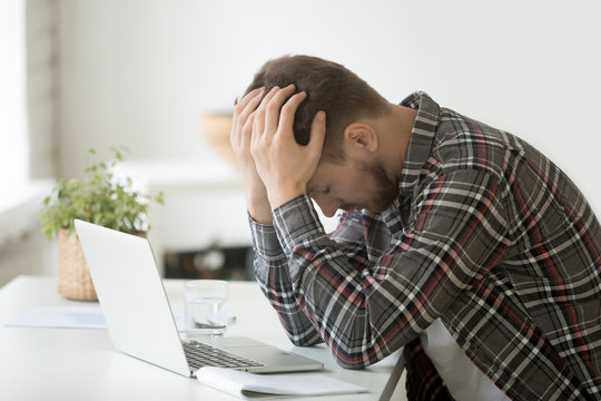 Frustrated depressed man holding head in hands shocked by bankruptcy stock downfall sitting at work desk with laptop, stressed tired businessman feels despair lost money online or got problem debt