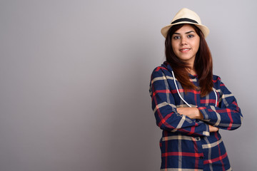 Young beautiful Indian tourist woman wearing checked shirt and h