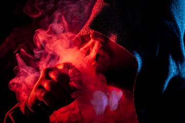 A handsome man in a black hood smokes and exhales large clouds of colored  red and blue smoke on a black isolated background
