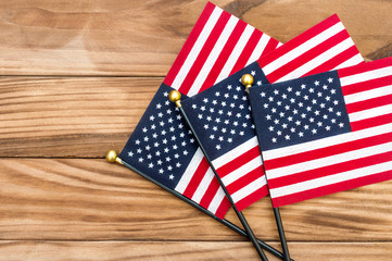 Three small american flags on wooden background. Top view. Copy space.