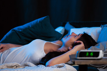 Image of young woman with insomnia lying on bed next to clock