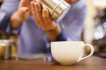 Photo of barista man pouring sugar into cup of coffee