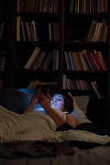 Image of woman with phone lying in bed at night