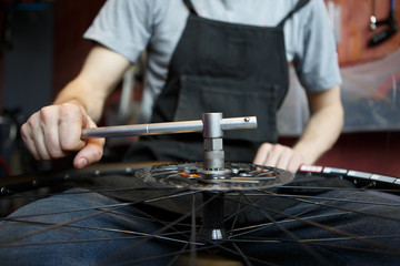 Photo of master repairing wheel of bicycle.