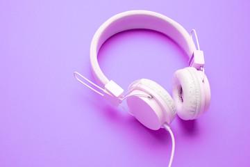 White headphones on empty purple background