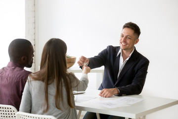 Happy interracial family couple getting keys to new house from realtor, satisfied clients buyers customers buying real estate property at meeting with agent, mortgage loan investment deal concept