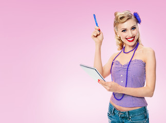 Smiling woman with notepad, in pin-up style clothing