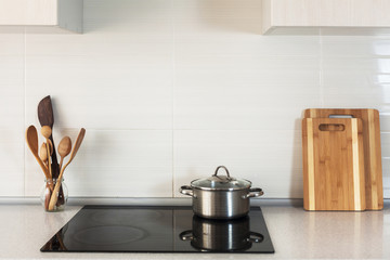 The pan is on a ceramic cooking plate in the new modern kitchen.