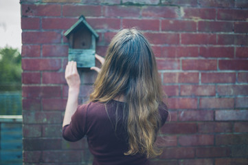 Woman touching bird house