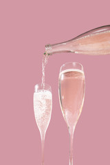 Valdobbiadene Prosecco flutes and a bottle, pink background, in pop contemporary style