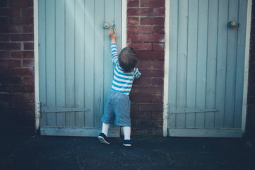 Toddler reaching for door handle in yard