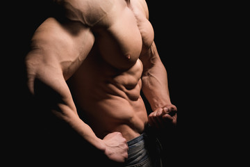 Fitness concept. Muscular and fit torso of young man having perfect abs, bicep and chest. Male hunk with athletic body on black background. Copypaste space