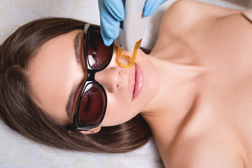 Young Woman Receiving Epilation Laser Treatment On Face At Beauty Center Close Up