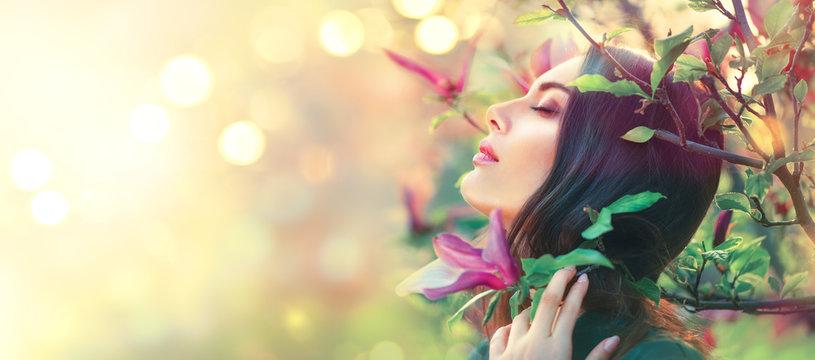 Happy beautiful girl enjoying nature. Blooming magnolia. Beauty young woman touching spring magnolia flowers