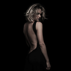 side view of beautiful blonde woman wearing black backless dress