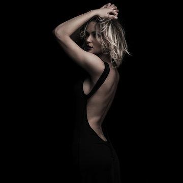 side view of elegant woman in black dress posing seductively