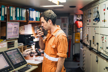 Marine Engineer working on radio communication at Engine Control room ECR. Vessel communication with VHF and UHF walkie-talkie radio