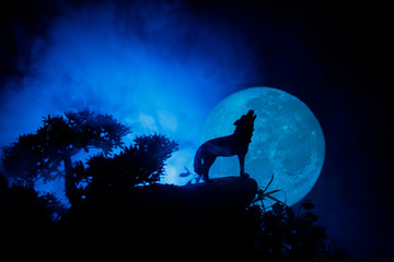 Wall Murals Wolf Silhouette of howling wolf against dark toned foggy background and full moon or Wolf in silhouette howling to the full moon. Halloween horror concept.