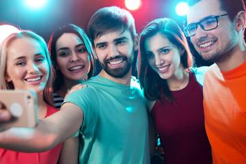 Group of happy friends taking selfie