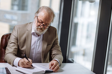 old professor with greyhair and beard in beautiful suit taking notes in the notebook in the room with panorama window