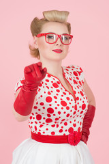 Smiled vivacious blond woman pointing at the camera in red gloves and glasses isolated on rose pink background