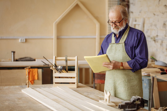 old grey headed joiner in work clothes is concentrated on making up project. making up plan. copyspace