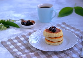 Curd cheese cakes with plum jam, sprinkled with powdered sugar.