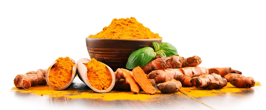 Bowl of turmeric powder over white background