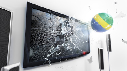 Soccer ball with the flag of Gabon kicked through a shattering tv screen.(3D rendering series)