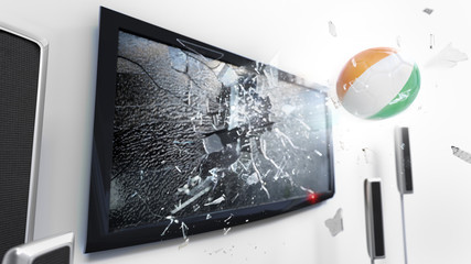Soccer ball with the flag of Ivory Coast kicked through a shattering tv screen.(3D rendering series)