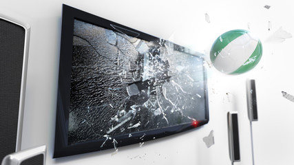 Soccer ball with the flag of Nigeria kicked through a shattering tv screen.(3D rendering series)