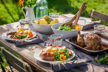 Dinner with chicken, salad and potatoes served in garden