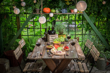 Preparation for dinner with wine and fruits in summer garden