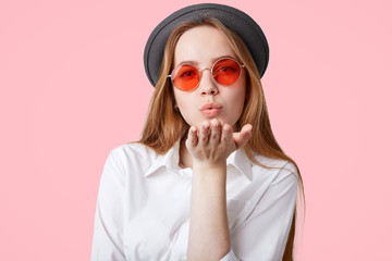 Lovely fashionable hipster girl wears trendy pink shades and black hat, blows air kiss at camera, poses against pink background, expresses her love to surrounding, Pleasant looking female flirts