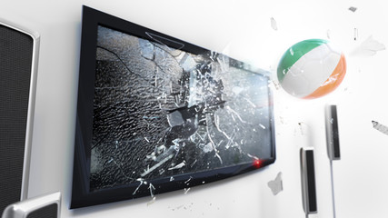 Soccer ball with the flag of Ireland kicked through a shattering tv screen.(3D rendering series)