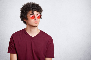 Youth, style and fashion concept. Attractive male teenager with crisp dark bushy hair, wears trendy red sunglasses and casual t shirt, poses against white studio background with blank copy space