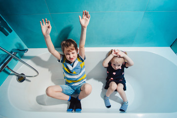 Kids sitting in bathtub and looking upward at camera. Little boy and girl playing inside a bathtub at home.
