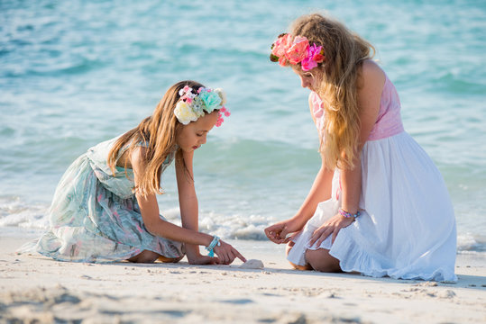 Two teenager girls playing on sand at the sea shore