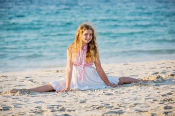 Cute young girl doing split at the beach