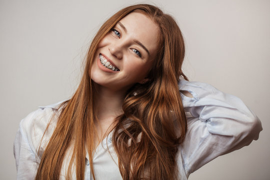 Happy young red-haired woman in braces smiling on white background looking at camera