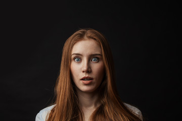 Surprised shoked young red haired girl with bugged blue eyes, isolated on black background