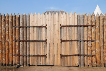 Traditional old russian closed wooden gate  with iron hinges. Large ancient medieval wooden gateway with the wooden fence over sky background.Countryside scene.Retro design.