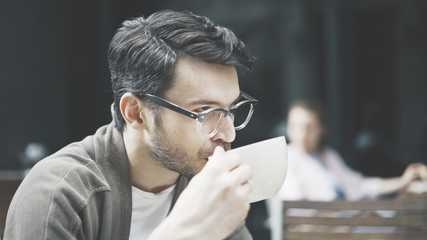A profile of handsome man dressed in a gray jacket and white shirt wearing eyeglasses outdoors drinking a cup of coffee