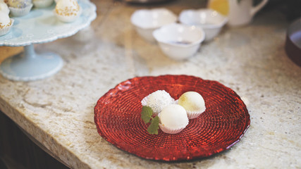Three sweets are on a red glass plate with a piece of mint on a kitchen table. Three decorated white chocolate sweets
