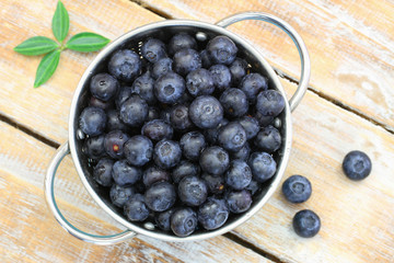 Fresh blueberries in aluminum colander on rustic wooden surface