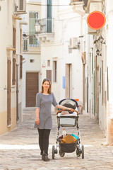 Gallipoli, Apulia - A woman out for a walk with her baby in the streets of Gallipoli