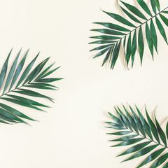 Leaf pattern. Green tropical palm leaves on pastel yellow background. Summer concept. Flat lay, top view, copy space, square