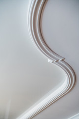 Curved decorative clay stucco relief molding on white ceiling in abstract classical style interior